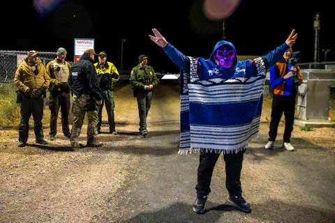 A costumed man stands near security personnel outside the back gate of Area 51 in homage to the ...