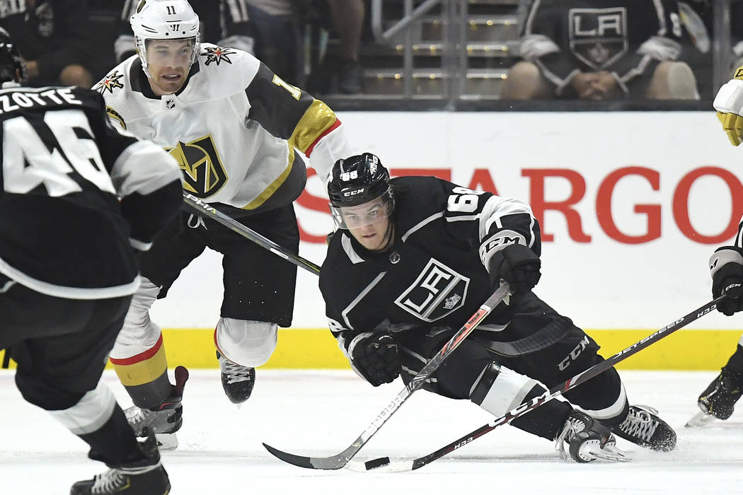 Los Angeles Kings left wing Samuel Fagemo, right, passes the puck as he falls, while Vegas Gold ...