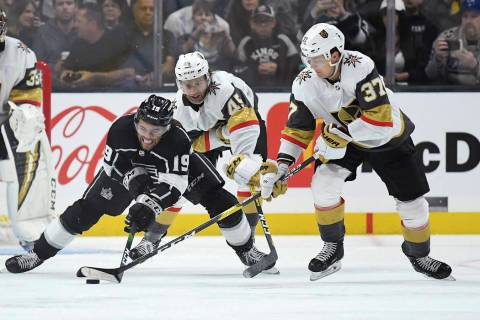 Los Angeles Kings left wing Alex Iafallo, left, tries to pass the puck while under pressure fro ...