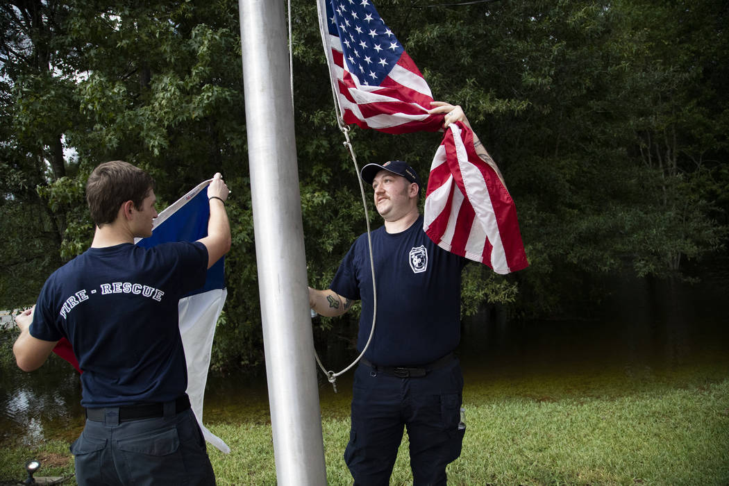 Caney Creek Fire Department firefighters Avery Aultman, 21, left, Luke Hancock, 24, right, rais ...