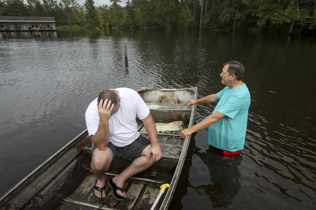 Stephen Gilbert, left, and his father-in-law sit in front of their flooded property on Friday, ...