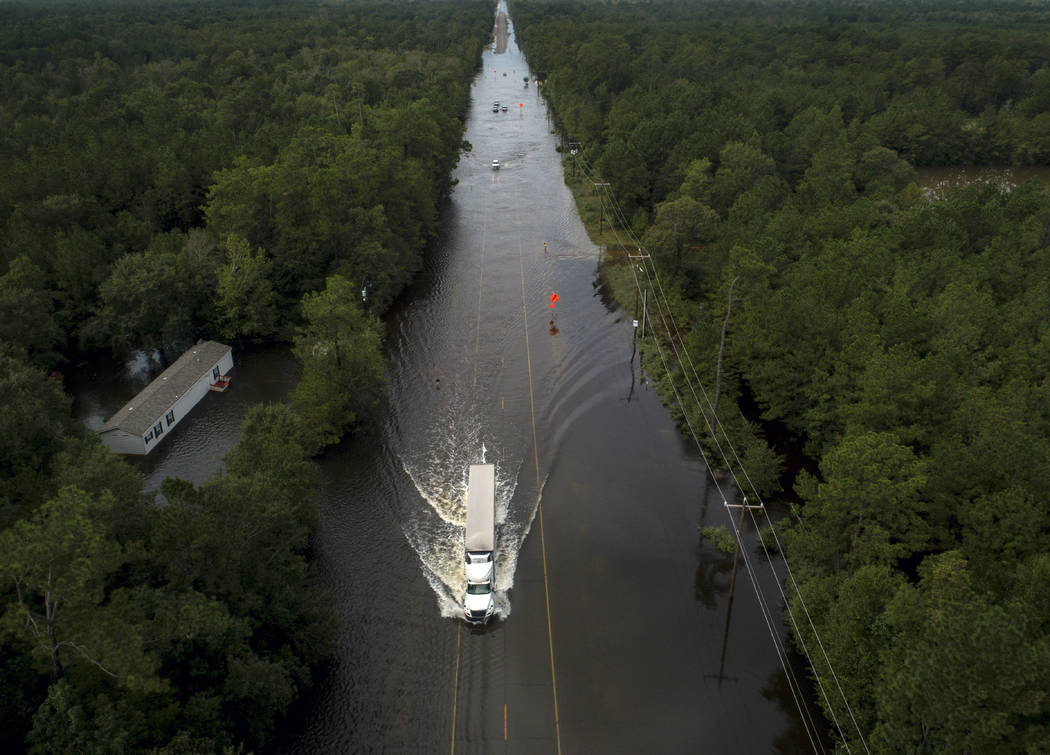 A truck drives through a flooded highway as flooding from the remnants of Tropical Storm Imelda ...