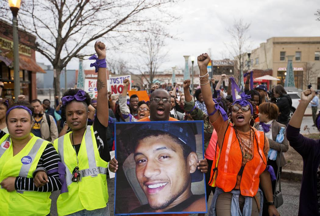 FILE - In this March 11, 2015 file photo, Brandon Marshall carries a photo of Anthony Hill as p ...