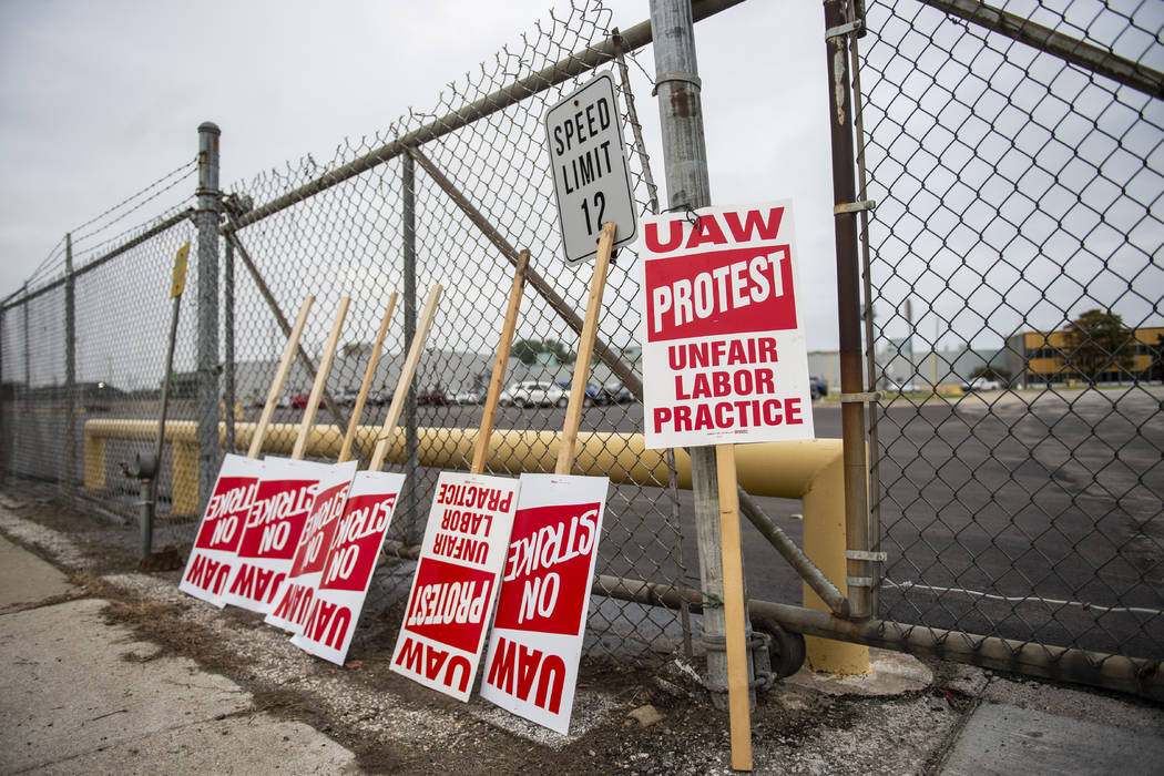 United Auto Workers protest signs lean against the fence at GM Powertrain in Bay City, Mich., o ...