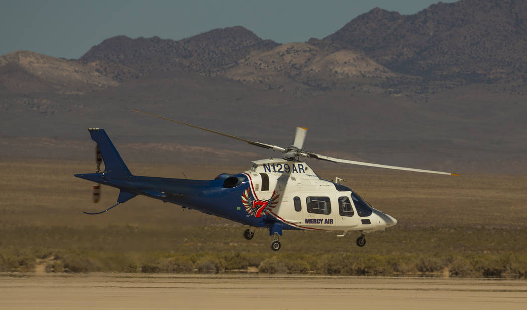 A Mercy Air helicopter lifts off with two injured in a vehicle rollover on the salt flats just ...