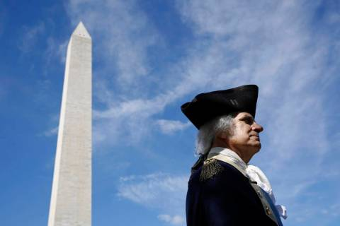 John Lopes, playing the part of President George Washington, stands near the Washington Monumen ...