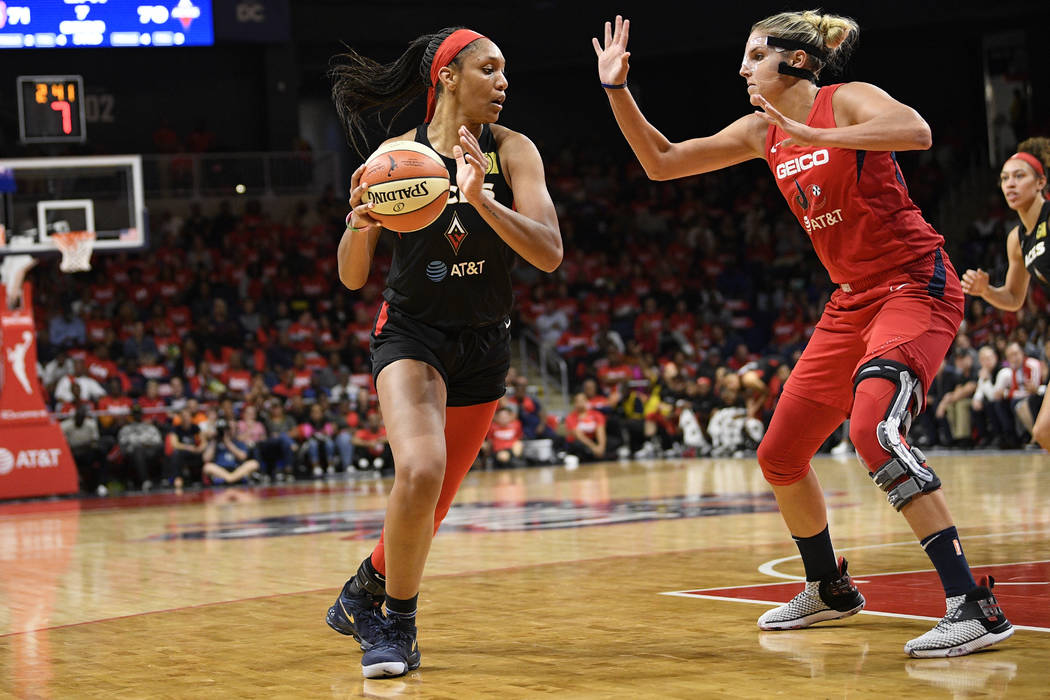 Las Vegas Aces center A'ja Wilson, left, dribbles the ball against Washington Mystics forward E ...