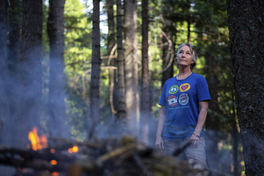 In this photo taken June 13, 2019, is Kelly Loew creating a defensible space around her home in ...