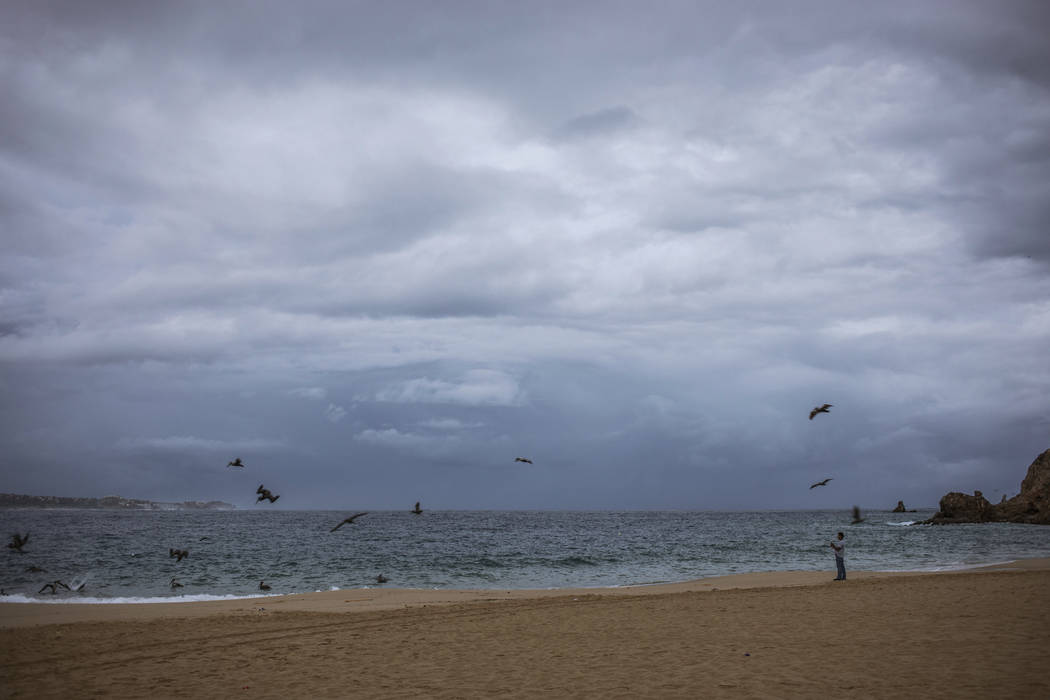 A tourist walks on the beach before the expected arrival of Hurricane Lorena, in Los Cabos, Mex ...