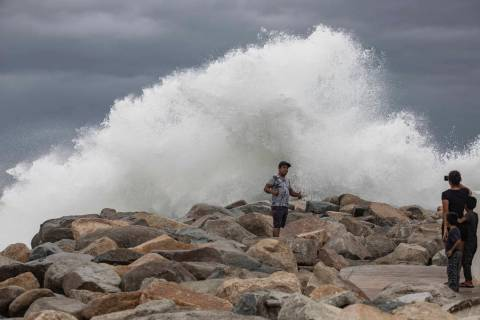 A tourist poses for a photo in front breaking waves before the expected arrival of Hurricane Lo ...