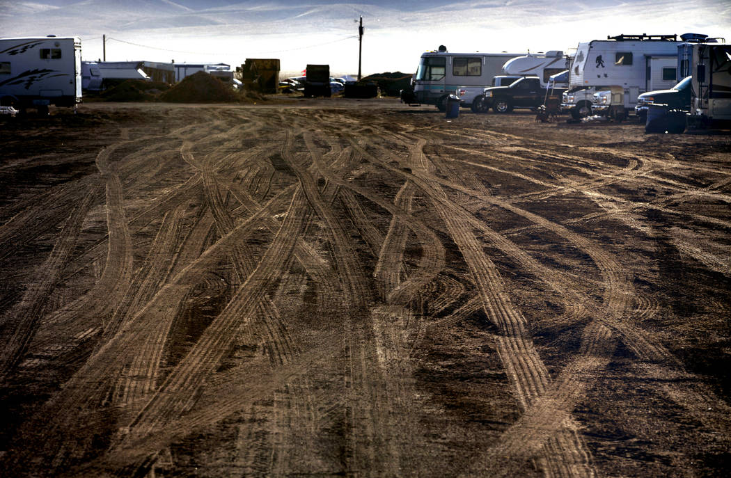 Morning falls on vehicle tracks in the RV parking area during the Alienstock festival on Saturd ...