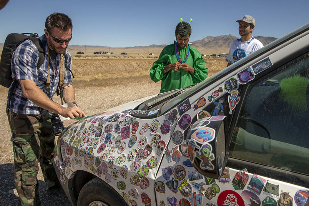 Festivalgoers add stickers to a car parked on the frontage road during the Alienstock festival ...