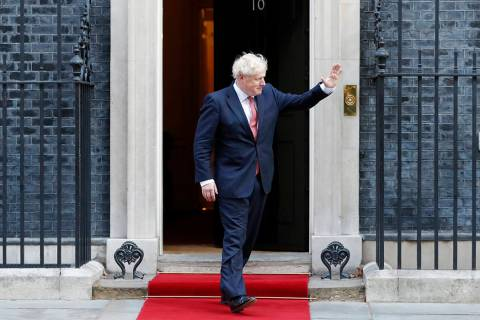 Britain's Prime Minister Boris Johnson waves to welcome the Emir of Qatar, Sheikh Tamim bin Ham ...