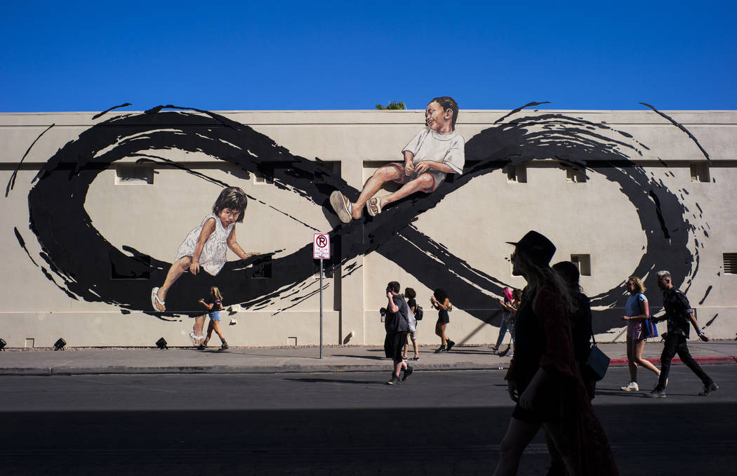 Attendees pass by a mural by Ernest Zacharevic during day 2 of the Life is Beautiful festival i ...