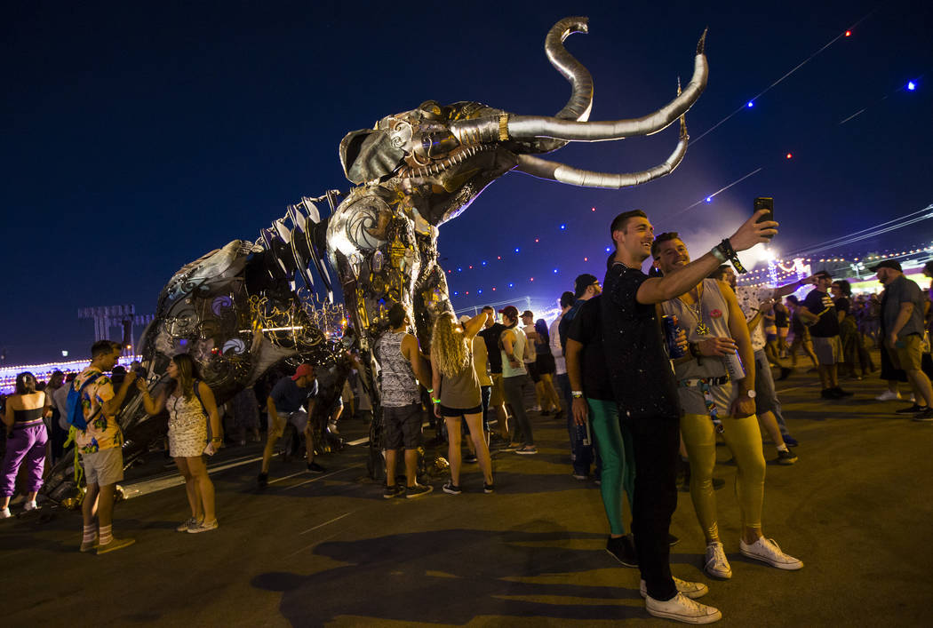 Attendees take pictures by the Monumental Mammoth sculpture, created by Tahoe Mack, during day ...