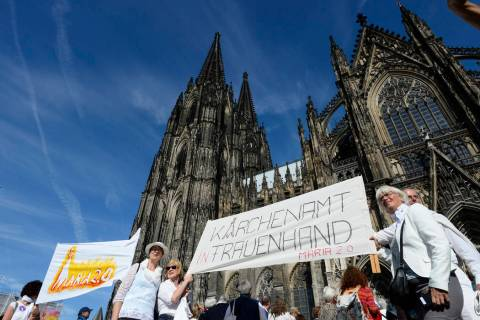 Protesters build a human chain in front of the Cologne Cathedral in Cologne, Germany, Sunday, S ...