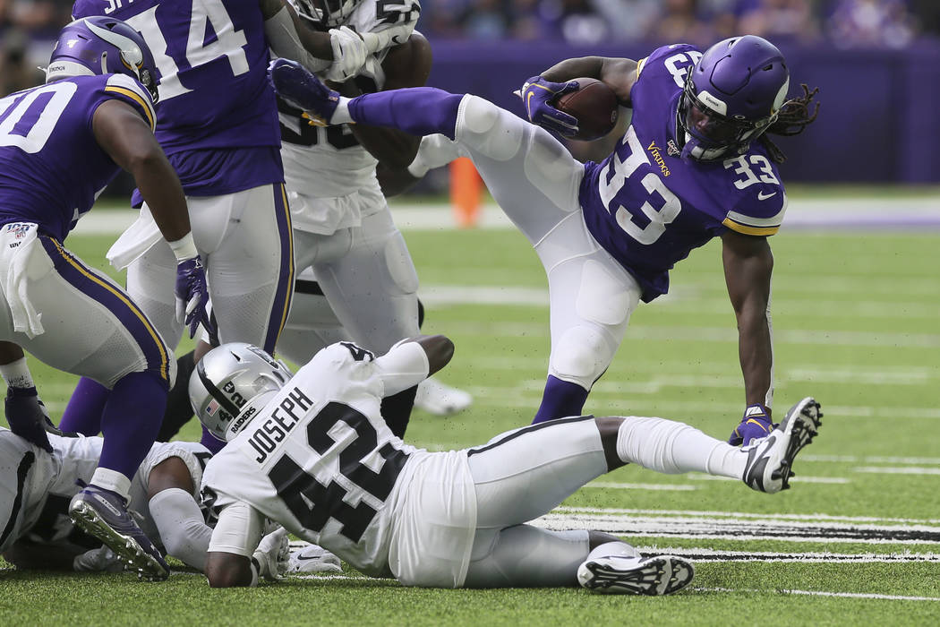 Minnesota Vikings running back Dalvin Cook (33) is upended by Oakland Raiders free safety Karl ...