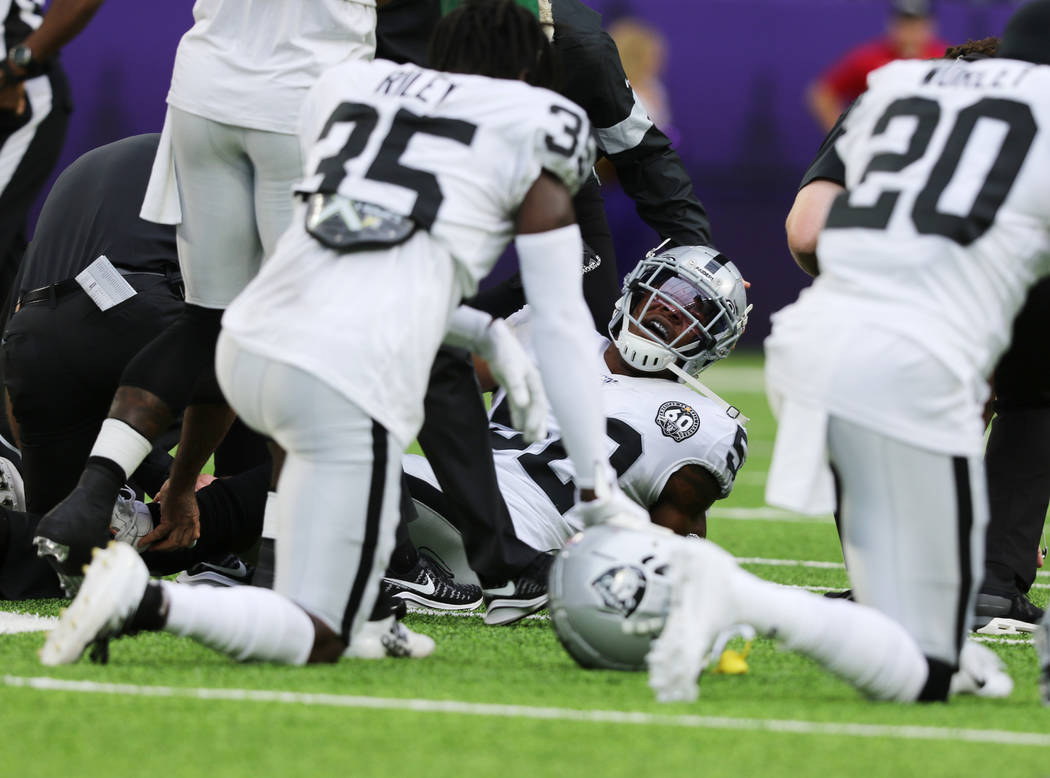 Oakland Raiders middle linebacker Marquel Lee (52) is tended to by trainers after being injured ...