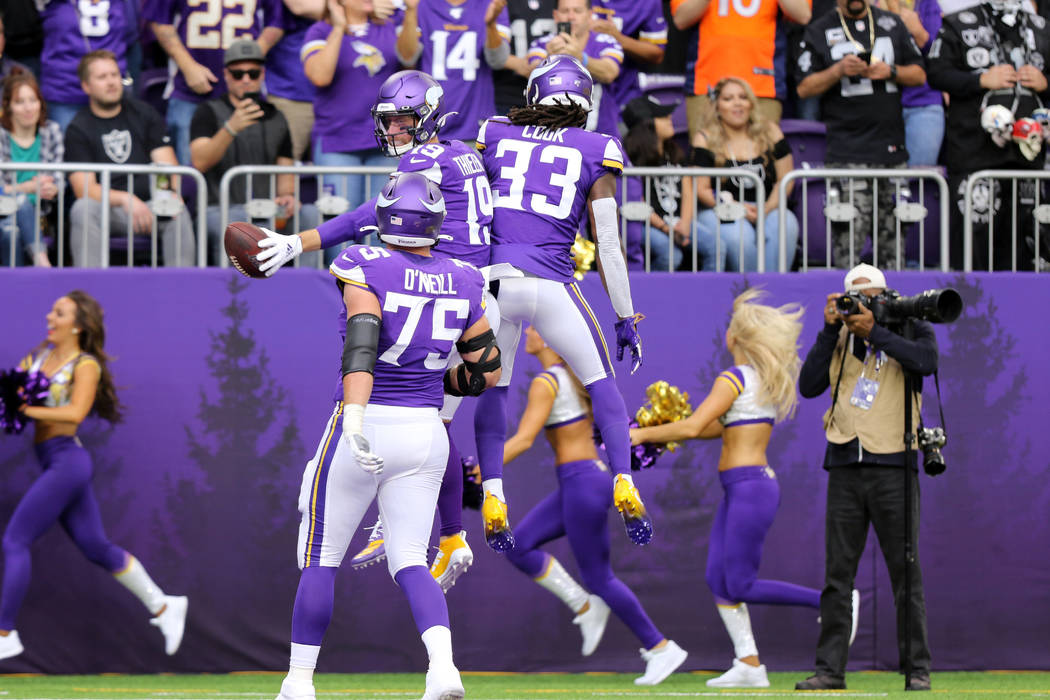 Minnesota Vikings wide receiver Adam Thielen (19) jumps in the air with running back Dalvin Coo ...