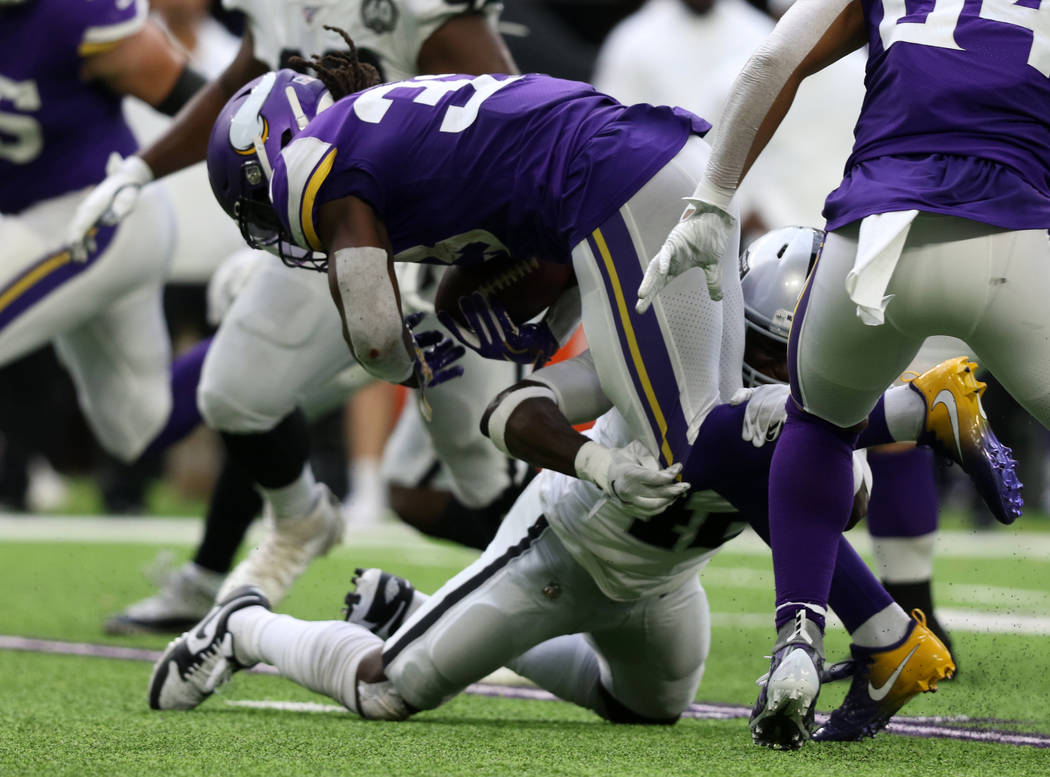 Minnesota Vikings running back Dalvin Cook (33) is tackled by Oakland Raiders free safety Karl ...