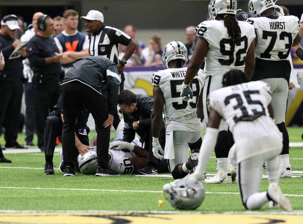 Oakland Raiders defensive tackle Johnathan Hankins (90) is helped on the field by trainers afte ...