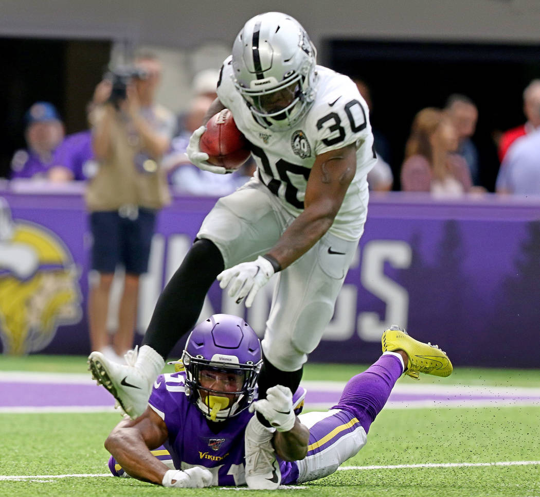 Oakland Raiders running back Jalen Richard (30) tries to shed a tackle from Minnesota Vikings r ...