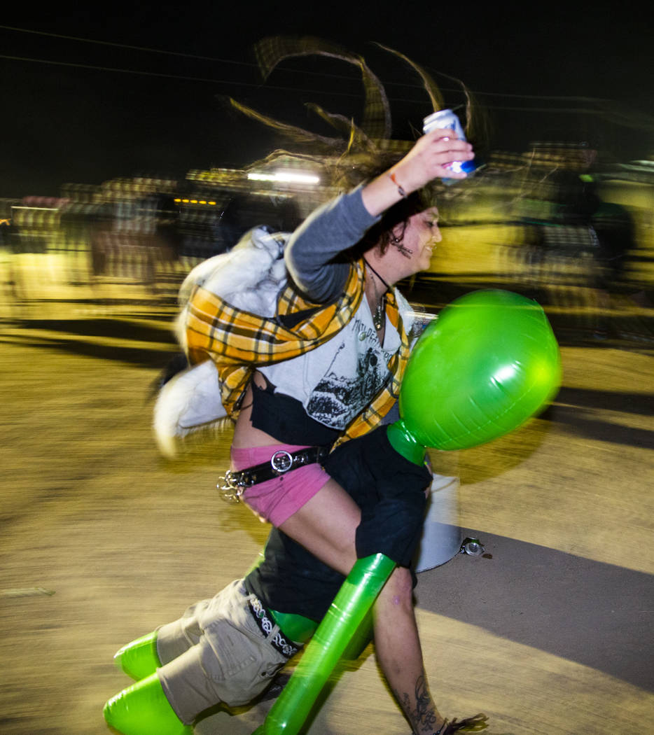 A festivalgoer rides an alien while drinking a beer in the mosh pit at the punk rock stage duri ...