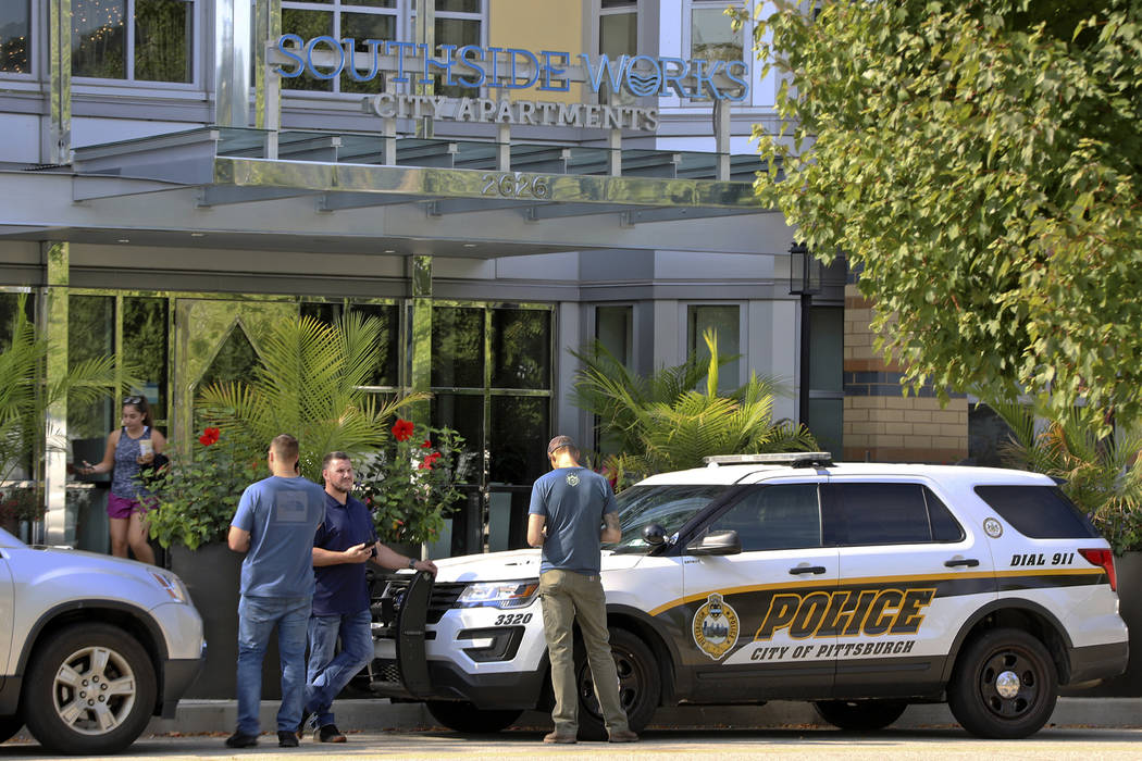 Pittsburgh police investigators gather outside an apartment building on the city's South Side w ...