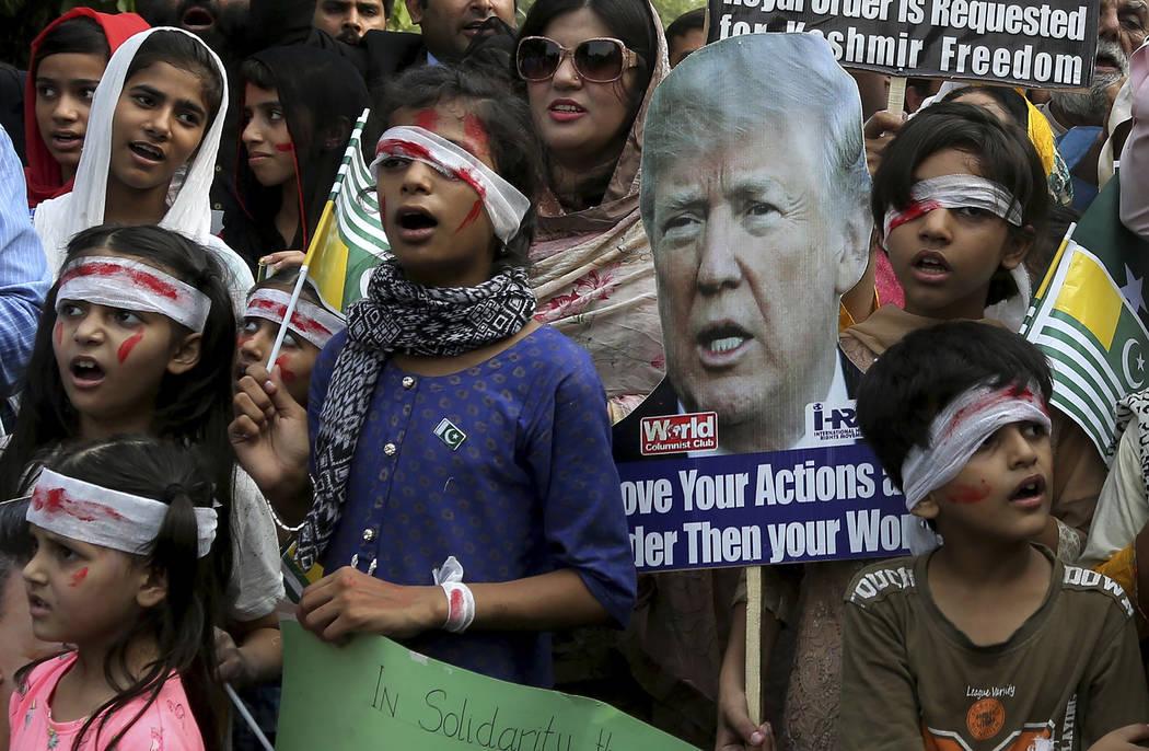 Pakistan children dress up like injured Kashmiri children and hold a portrait of U.S. President ...