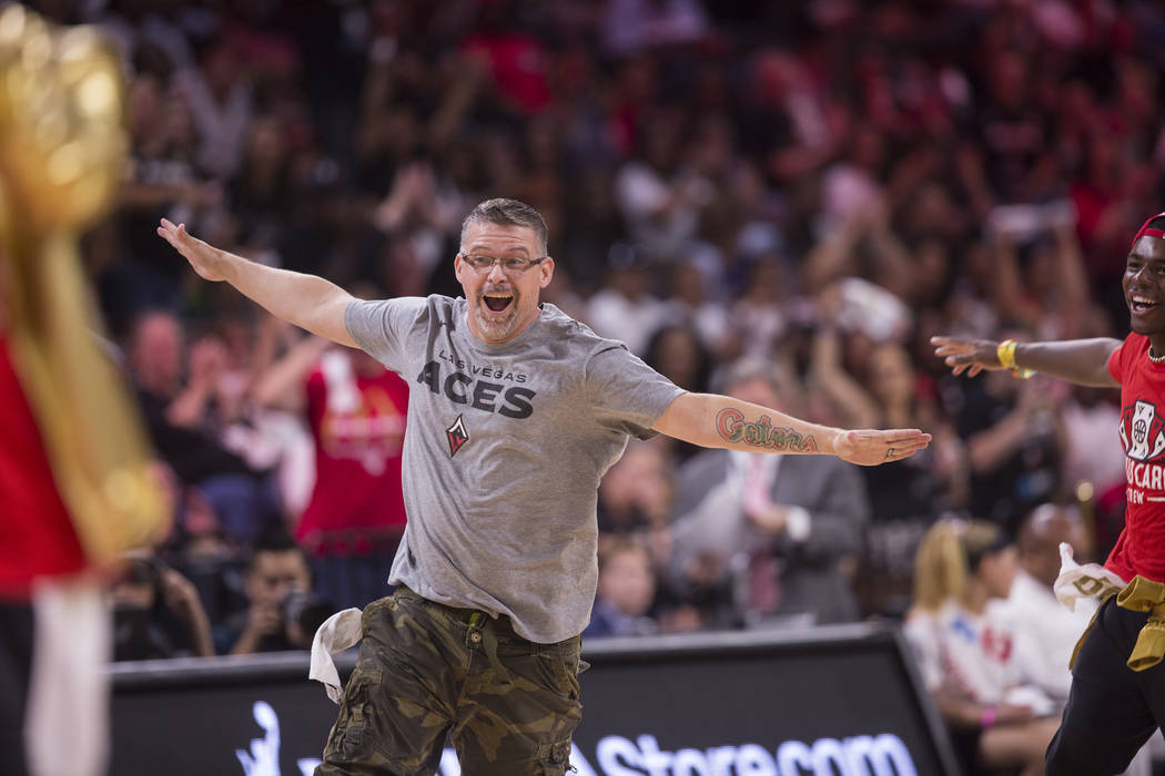 """Russ Canty celebrates after winning a """"pop-a-shot"""" contest during Vegas' WNBA semifin ..."""