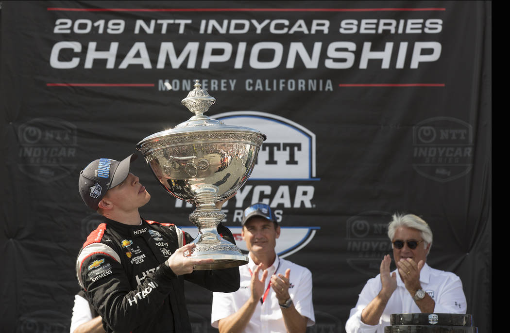 Josef Newgarden, left, kisses the trophy after winning the championship after an IndyCar auto r ...