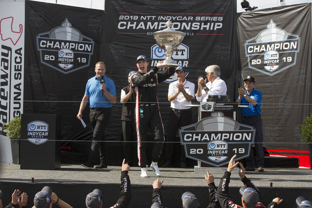 Josef Newgarden raises the trophy in the air after winning the championship after an IndyCar au ...