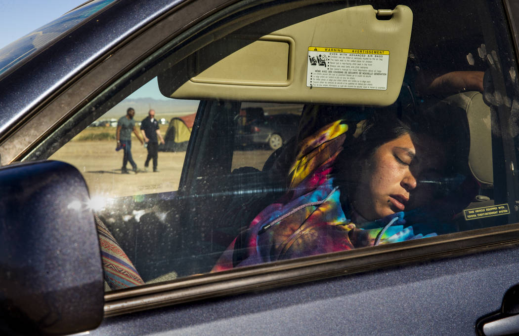 A festivalgoer sleeps in her car in the near-empty camping area during the Alienstock festival ...