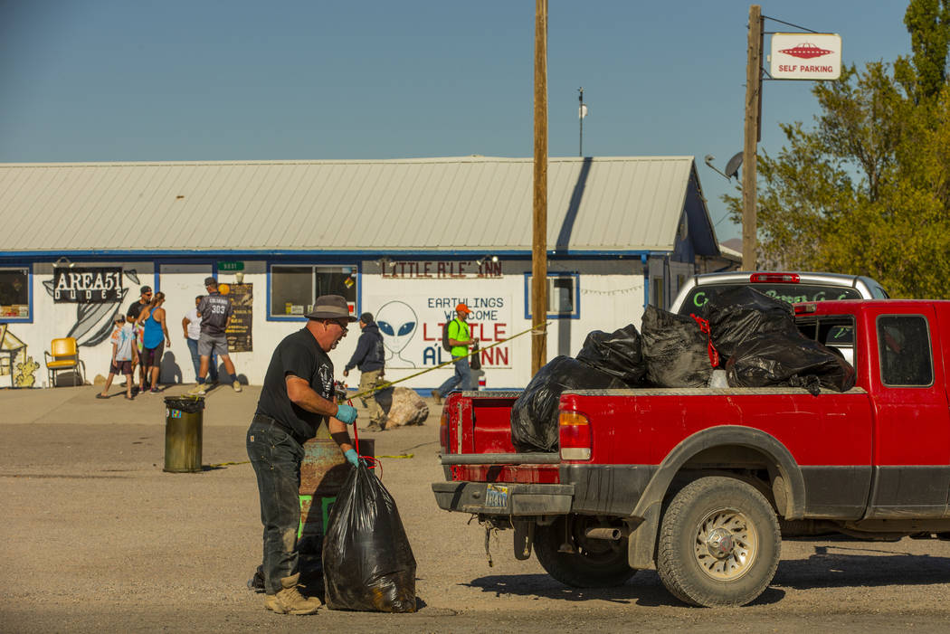 Kevin Dingo picks up bags of trash stacked in the parking area across from the Little A'Le'Inn ...