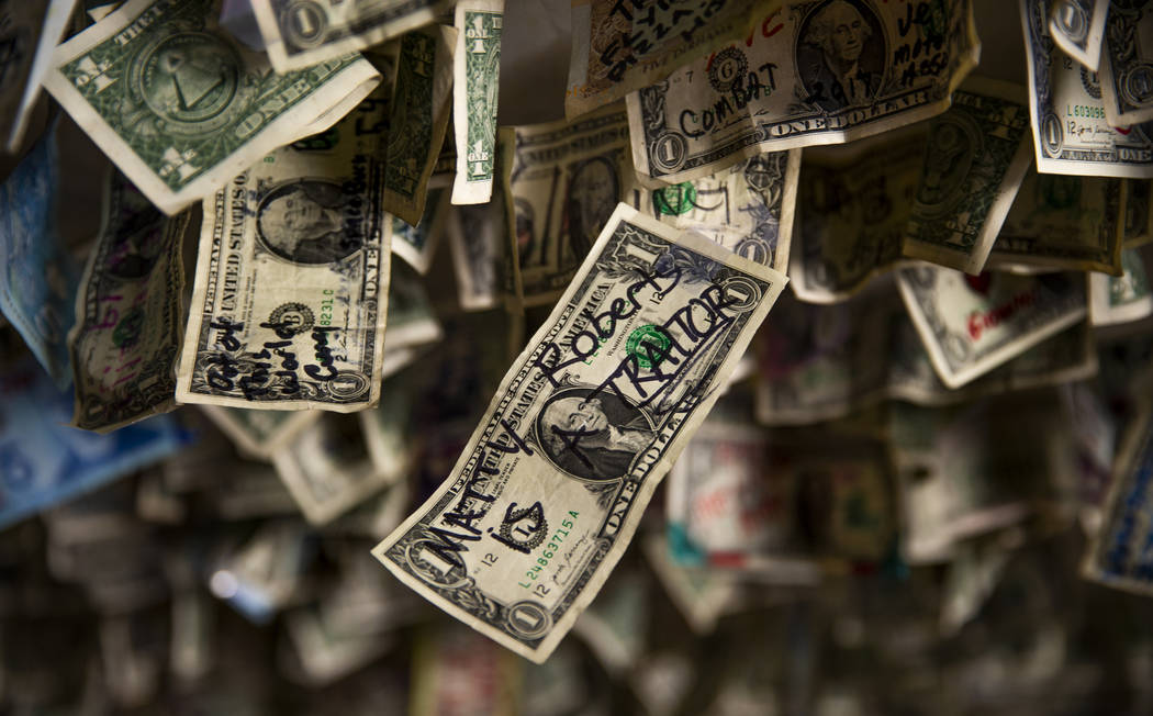 """A dollar bill written with """"Matty Roberts is a Traitor"""" hangs amongst many other from ..."""