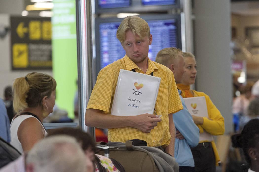Thomas Cook staff speak with British passengers at Palma de Mallorca airport on Monday Sept. 23 ...