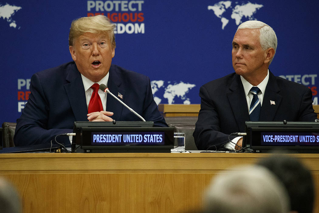 Vice President Mike Pence listens as President Donald Trump speaks at an event on religious fre ...