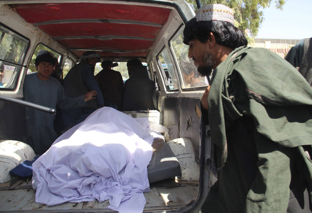 Afghans transport the body of a woman who was killed during a raid conducted by Afghan special ...