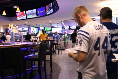 People wait in line to place bets at Winner's Circle sporstbook in Indianapolis, Ind., Sunday, ...