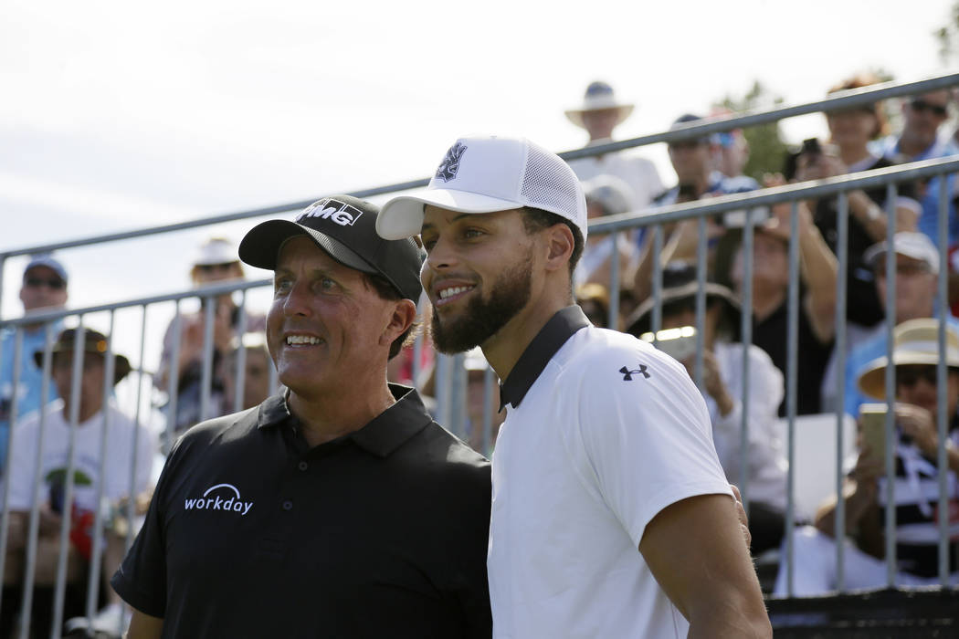 Phil Mickelson, left, and Stephen Curry pose for pictures before hitting from the first tee of ...