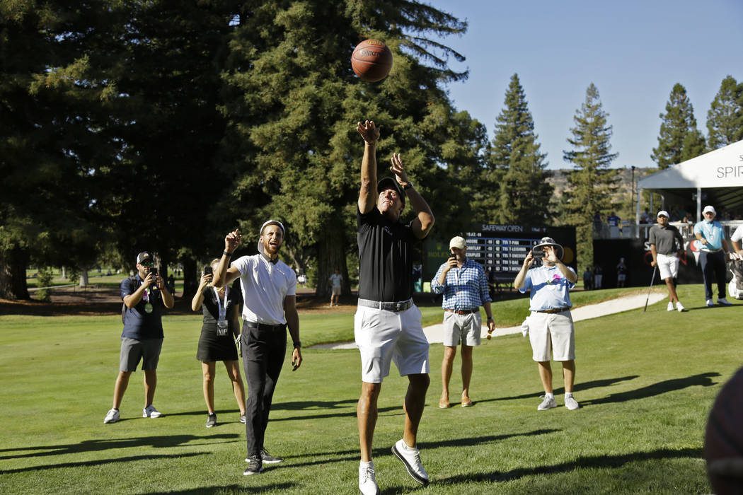 Phil Mickelson shoots a basketball below the 17th green of the Silverado Resort North Course as ...