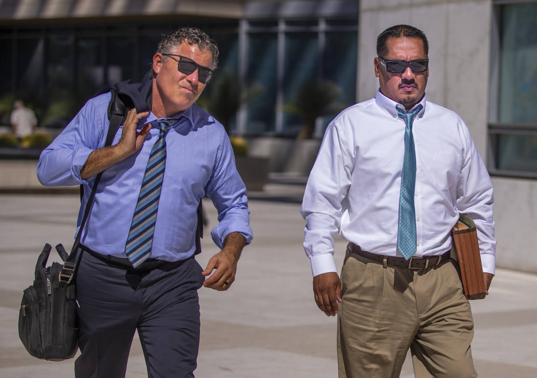 Counselor Mark Fleming, left, walks out with defendant Albert Lopez past defendant Bradley Camp ...