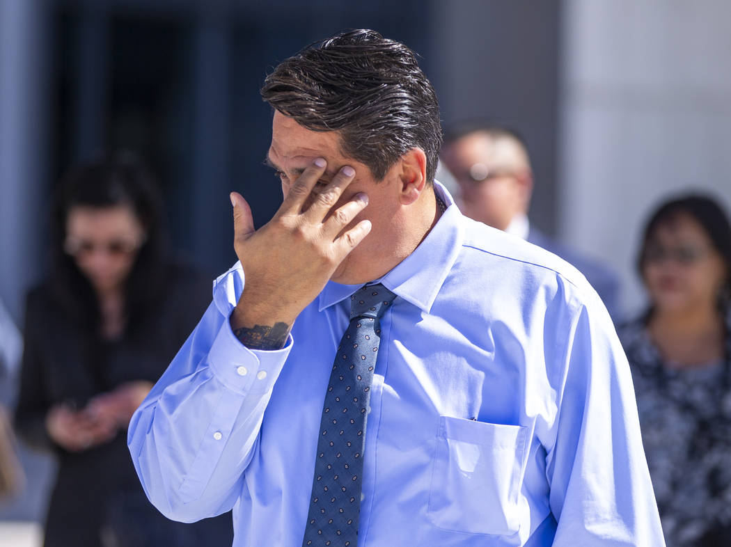 Defendant Bradley Campos hides his face while departing the Lloyd D. George Courthouse followin ...
