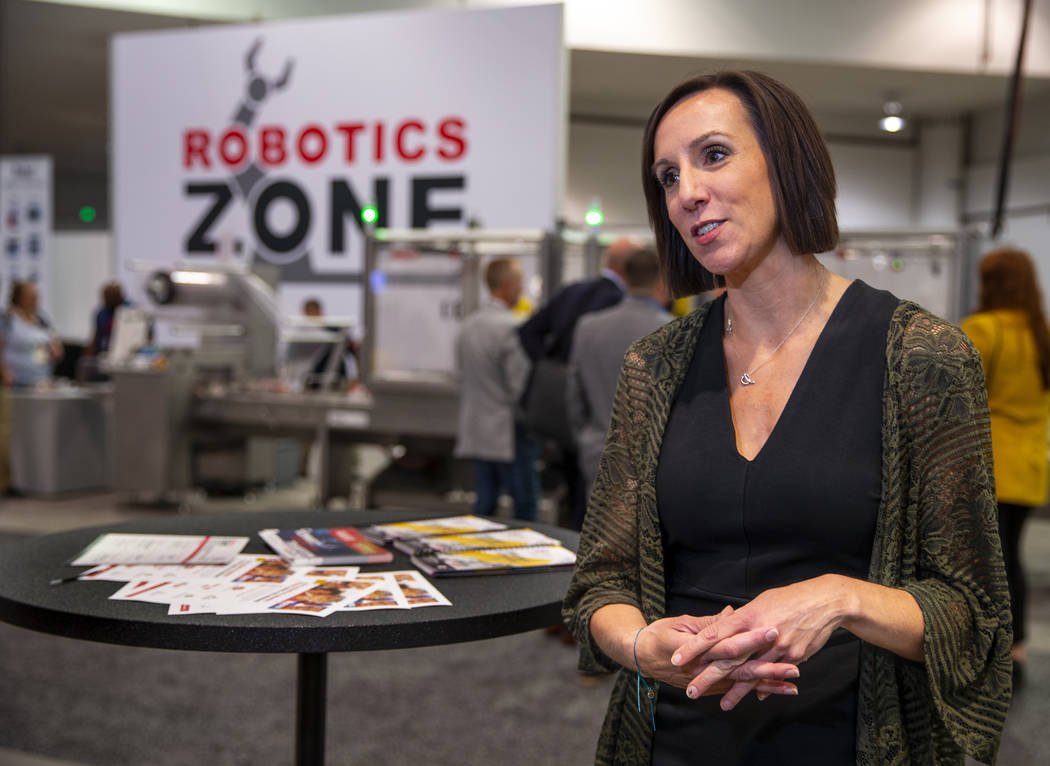 Laura Thompson with PMMI talks about the PACK EXPO and how the robots behind are packing school ...