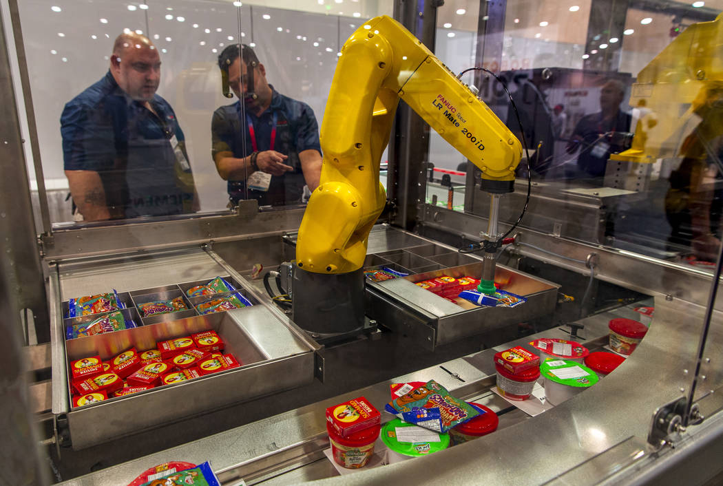 A robot with Bosch Packaging technology Inc. packs school lunches for kids through Blessings in ...