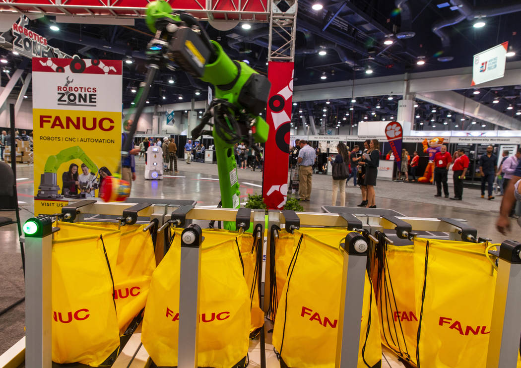 A robot from Fanuc packs school lunches for kids through Blessings in a Backpack at the PACK EX ...