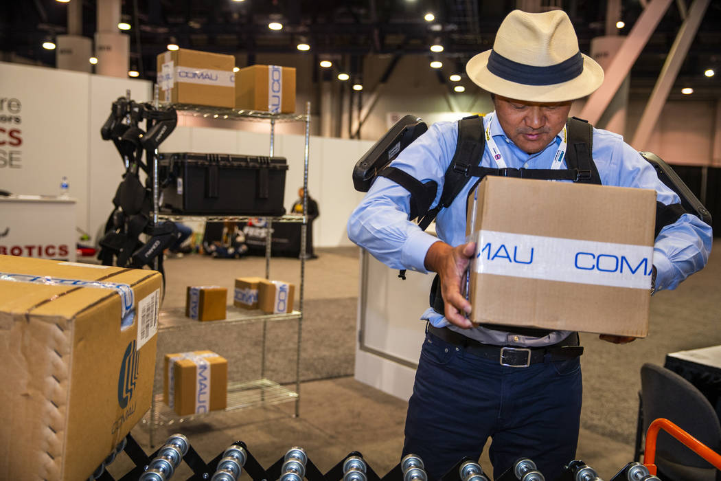 Attendee Toshiki Miyasaka lifts a box with the aid of a MATE Exoskeleton robotic apparatus at P ...