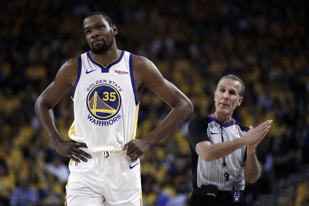 Golden State Warriors' Kevin Durant, left, walks away from referee Ken Mauer during the first h ...
