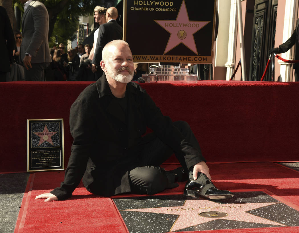 Screenwriter/television producer/director Ryan Murphy poses behind his new star during a ceremo ...