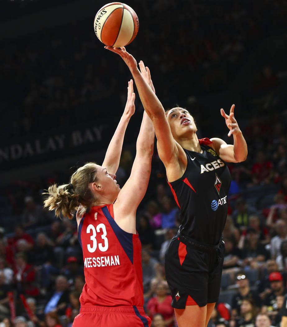 Las Vegas Aces' Dearica Hamby goes to the basket past Washington Mystics' Emma Meesseman (33) d ...